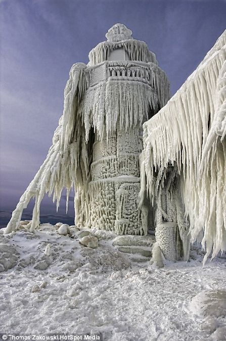 A lighthouse stands frozen still after a big storm in St Joseph, Michigan